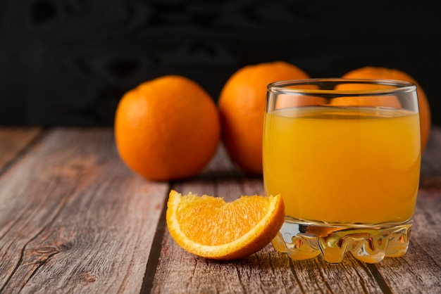 Orange fruit with a glass of juice on the wooden table