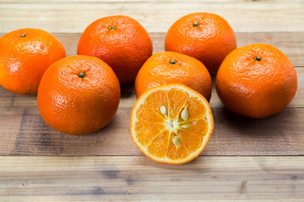 Orange fruit on wooden table with knife