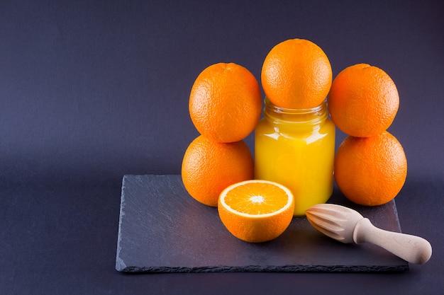 Orange fruits and juice. citrus fruit for making juice with manual juicer. oranges on slate board. mason jar with orange juice