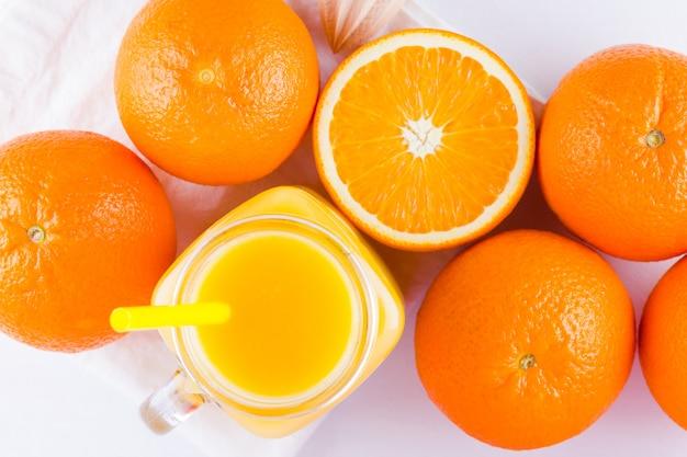 Orange fruits and juice. citrus fruit for making juice with manual juicer. oranges on white napkin. mason jar with orange juice