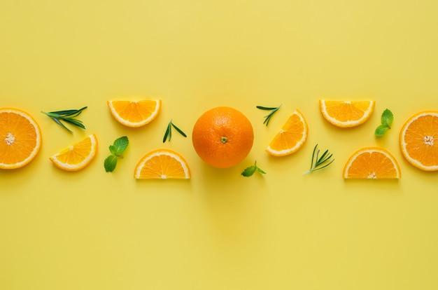 Оранжевые плоды с мятой и листьями розмарина на желтом фоне