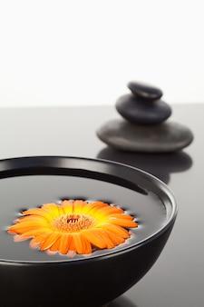 黒いボールと黒い小石のスタックに浮かぶオレンジのガーベラ