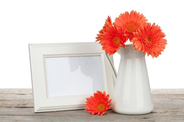 흰색 바탕에 나무 테이블에 오렌지 gerbera 꽃과 사진 프레임