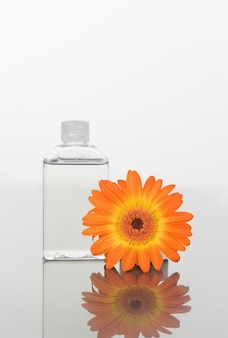 Orange gerbera and a glass flask on a mirror