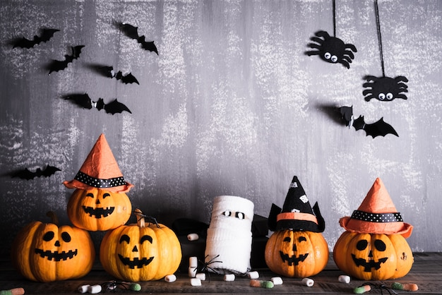Orange ghost pumpkins with witch hat on gray wooden board