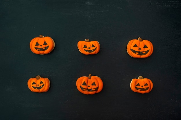Апельсиново-имбирное печенье на хэллоуин в виде тыквы лежит горизонтально на темном столе. улыбающееся печенье. вид сверху на стол.