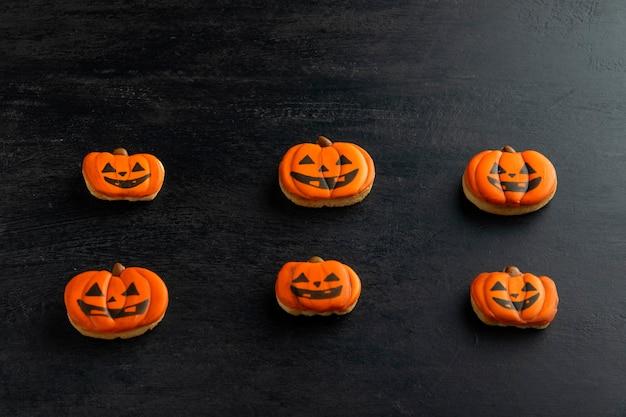 호박 모양의 할로윈을 위한 주황색 생강 쿠키는 어두운 탁자 위에 수평으로 놓여 있습니다. 웃는 쿠키. 평면도