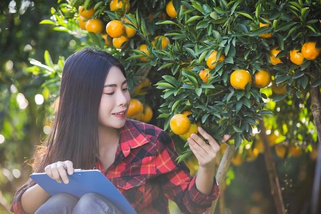 空のフォームを手で保持しているオレンジの女の子農家。