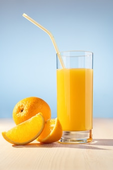 Orange, glass with orange juice and straw on wooden table.