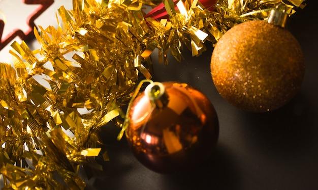 オレンジゴールドの光沢のあるクリスマスボール、背景にゴールドのガーランド、バックライト