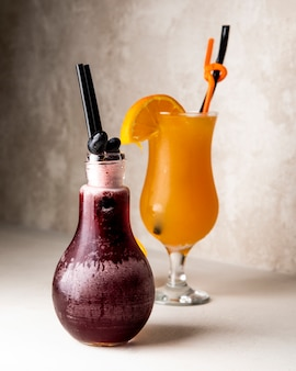 Orange and grape juices with fruits inside glass and jar.