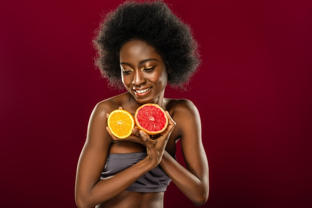 Orange and grapefruit. attractive afro american woman smiling while having fruits in her hands