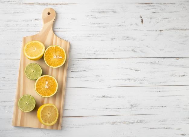 オレンジ、グリーンレモン、シチリアレモンは、コピースペースのある木の板をカットします。