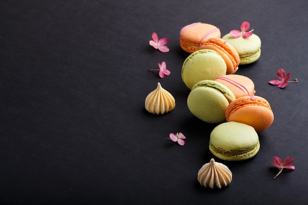 Orange and green macarons or macaroons cakes on black background, side view, copy space.
