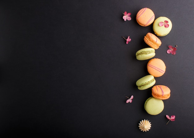 Orange and green macarons or macaroons cakes on black background, top view, copy space.