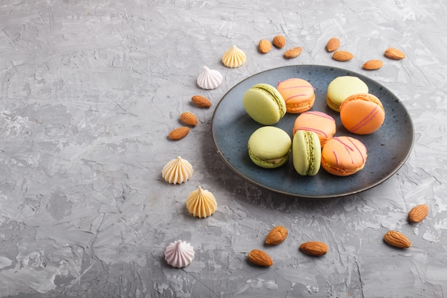 Orange and green macarons or macaroons cakes on blue ceramic plate on a gray concrete background. side view.