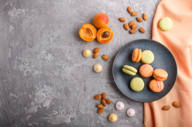 Orange and green macarons or macaroons cakes on blue ceramic plate on a gray concrete background, top view.