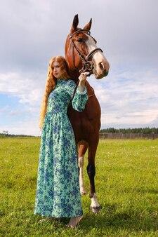 Оранжевая женщина волос и ее коричневая лошадь в области, просто расслабляющейся в летний день