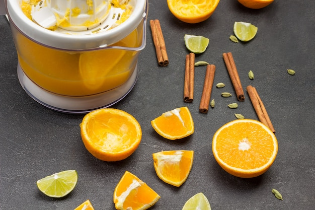 テーブルの上のオレンジ色の半分とスパイス。既製ジュースとジューサー。黒の背景。上面図