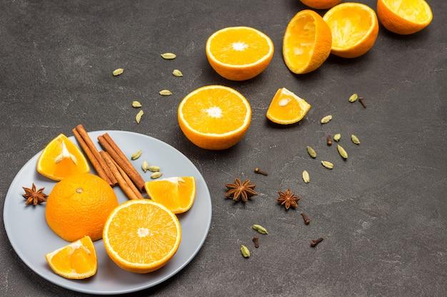 Половинки апельсина, палочки корицы и звездчатый анис на серой тарелке. специи на столе. апельсины и кожура на столе. черный фон. скопируйте пространство. вид сверху.