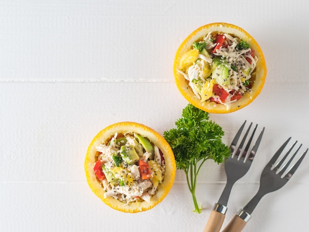 Половинки апельсина с салатом, двумя вилками и зеленью на белом столе. диетическое питание из тропических фруктов и курицы.