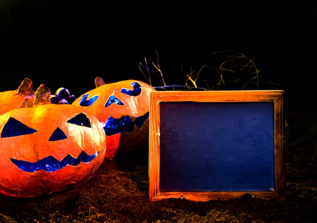 Orange handmade pumpkins in halloween style with carved faces lying next to empty photo frame