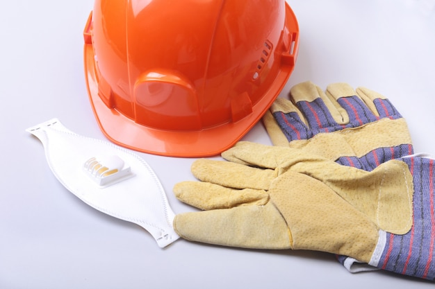 Orange hard hat, goggles, protective mask, respirator and safety gloves on a white background.