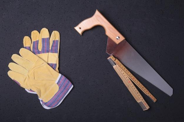 Orange hard hat, safety glasses, gloves, saw and measuring tape.
