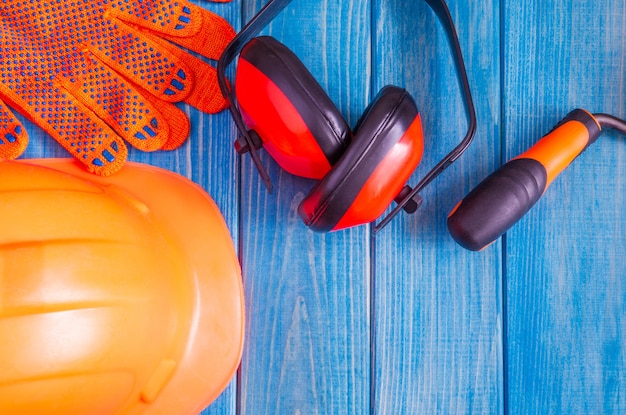 Orange hard hat and tools on wooden blue boards, flat lay