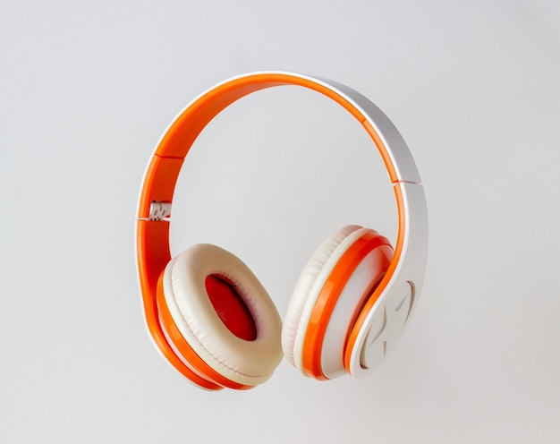 白い壁にオレンジ色のヘッドフォン