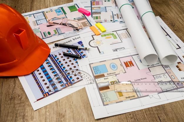 オレンジ色のヘルメット、建築図面、電卓、ペン
