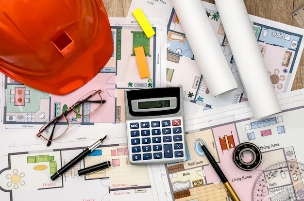Orange helmet, construction drawing, calculator, pen