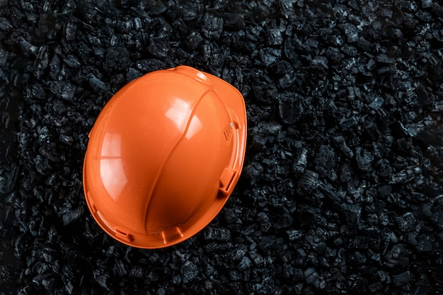 An orange helmet of a miner lies on a heap of coal, open pit coal mining, copy space.