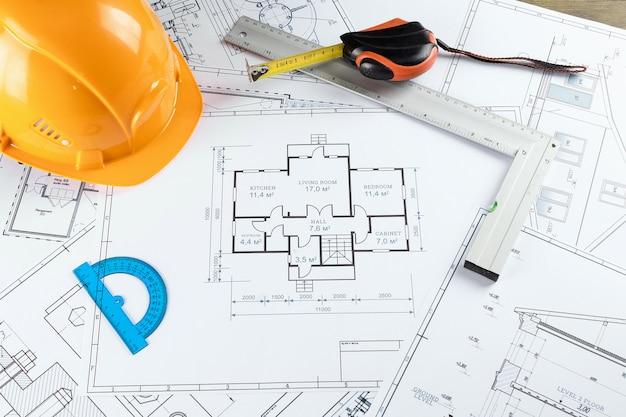 Orange helmet, pencil, architectural construction drawings, tape measure