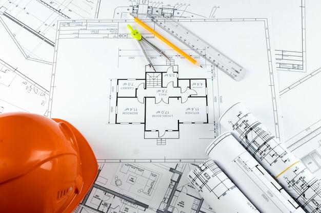 Orange helmet, pencil, architectural construction drawings, tape measure.