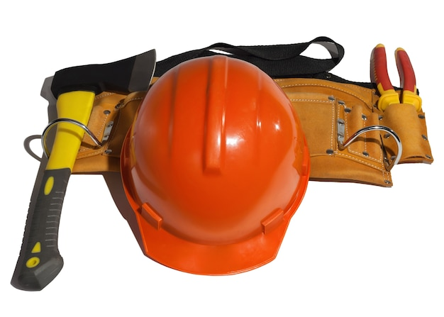 Orange helmet next to the tools in leather belt on a white
