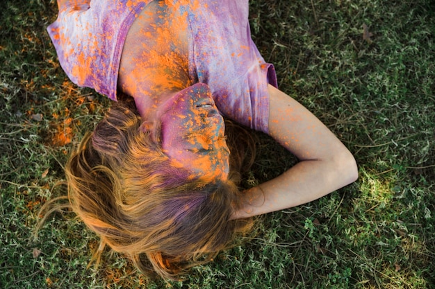 An orange holi color on woman's face lying on green grass