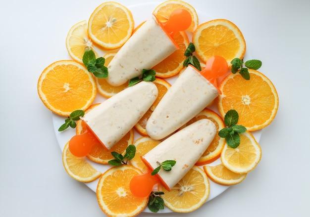 オレンジアイスクリームとプレート上のオレンジスライス Premium写真