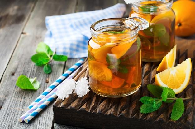 민트와 오렌지 아이스 티는 오래 된 나무 배경에 유리 항아리에 나뭇잎. 선택적 초점.