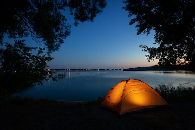 Оранжевый свет внутри палатки в окружении силуэтов ветвей деревьев на озере ночью