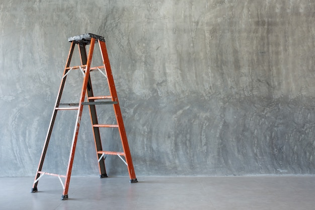 Orange iron ladder  on bare cement wall