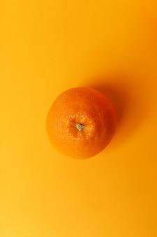 Апельсин, изолированные на оранжевой поверхности