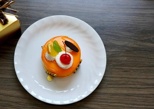 オレンジジャムケーキに部分的にホイップクリームをトッピングし、レッドチェリーオレンジのピースとチョコレートプレートを添えました