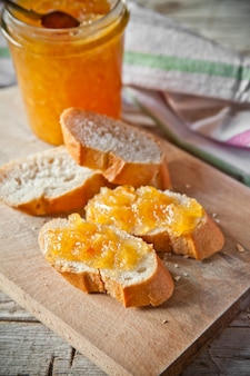 Orange jam in a glass jar and bread