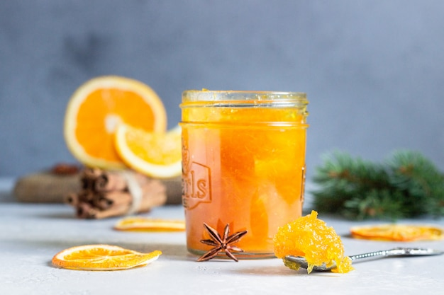 Orange jam in a glass jar with winter spices and fir branches.