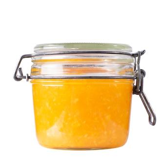 孤立した背景の瓶の中のオレンジジャム。