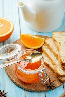 Orange jam and ingredients on blue background