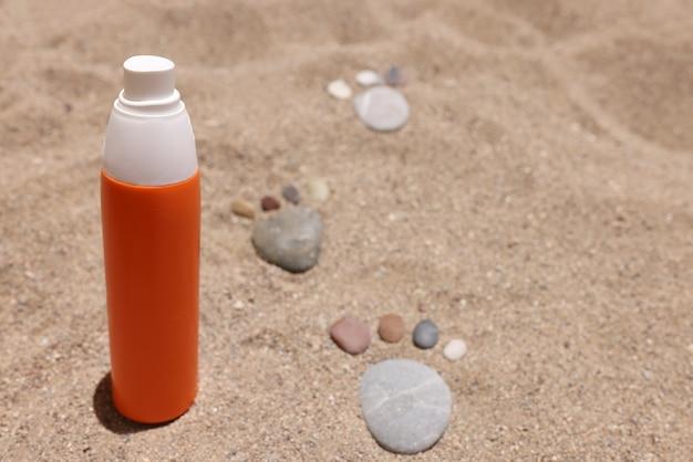 Оранжевая банка солнцезащитного крема, стоящая на песке возле каменных следов крупным планом