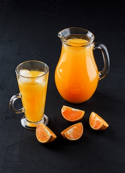 Orange juce in glass cup and jug with orange slices