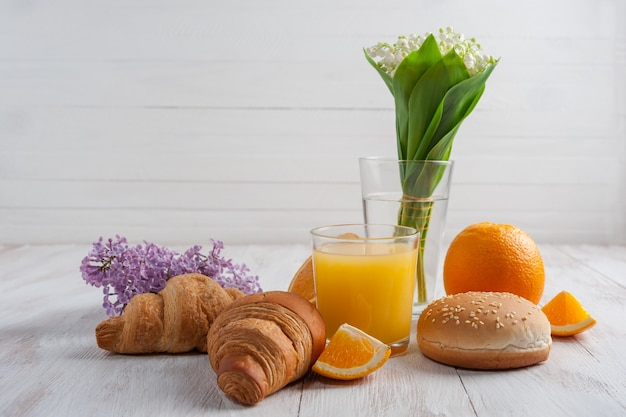 朝食にオレンジジュースとクロワッサン、ユリの花の装飾、コピースペース